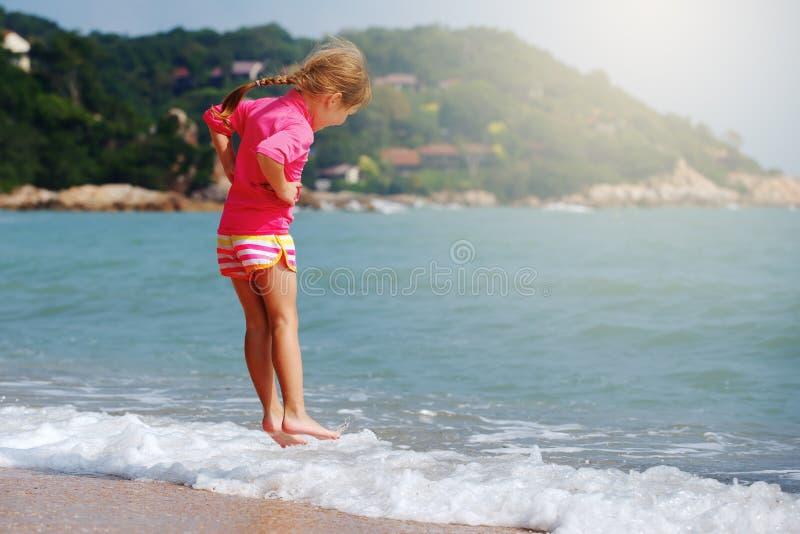 Счастливый ребенок играя в море стоковая фотография rf