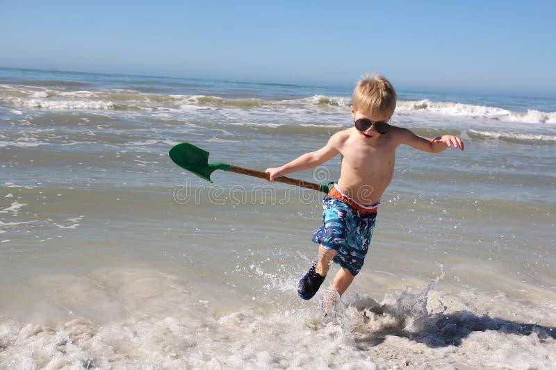 Счастливый ребенок играя в океанских волнах стоковые фото