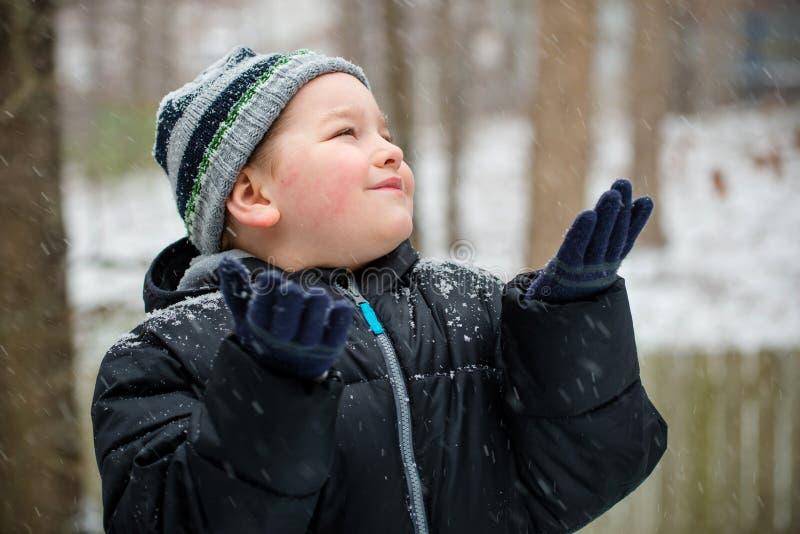 Счастливый ребенок играя в снеге стоковое изображение rf