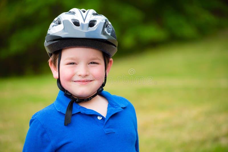 Счастливый ребенок нося шлем велосипеда стоковая фотография rf