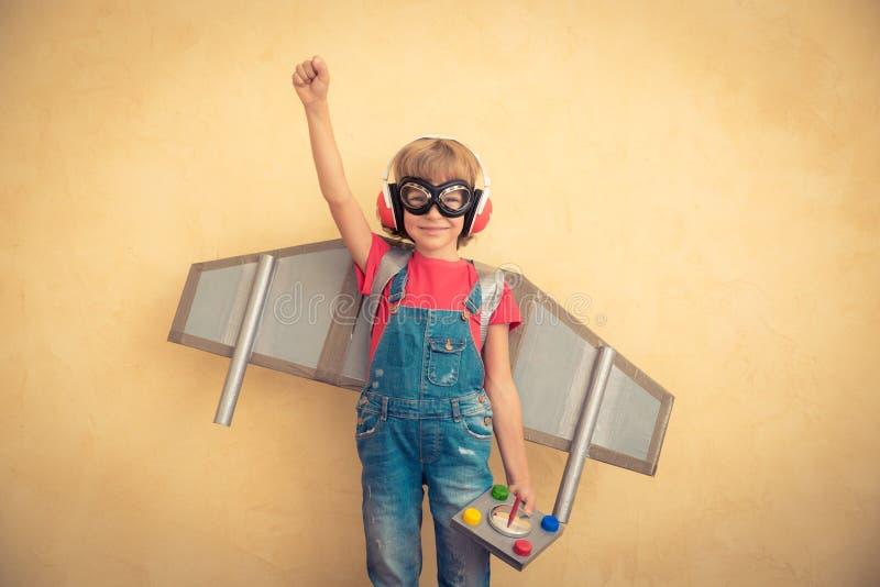Счастливый ребенок при jetpack игрушки играя дома стоковые изображения