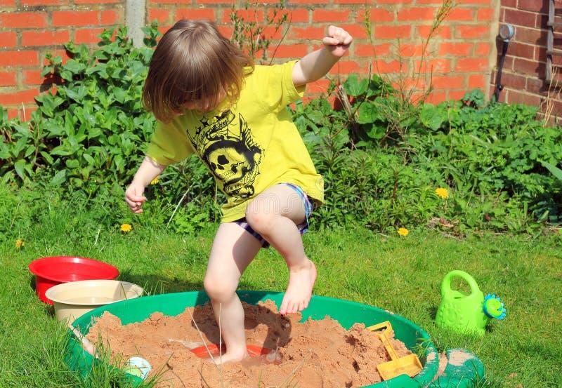 Счастливый ребенок скача в яму песка стоковое фото rf