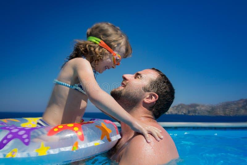 Счастливый ребенок с отцом в бассейне стоковое фото