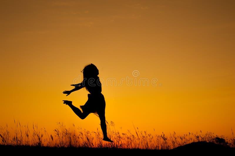 Download Счастливый силуэт скакать и захода солнца женщины Стоковое Фото - изображение насчитывающей девушка, женщина: 37931886