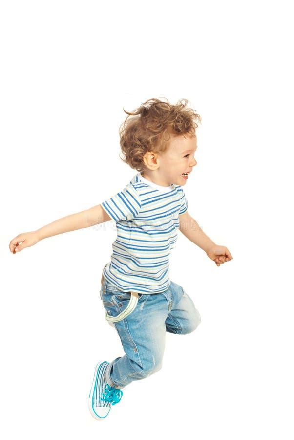 Счастливый скакать мальчика ребенк стоковое изображение
