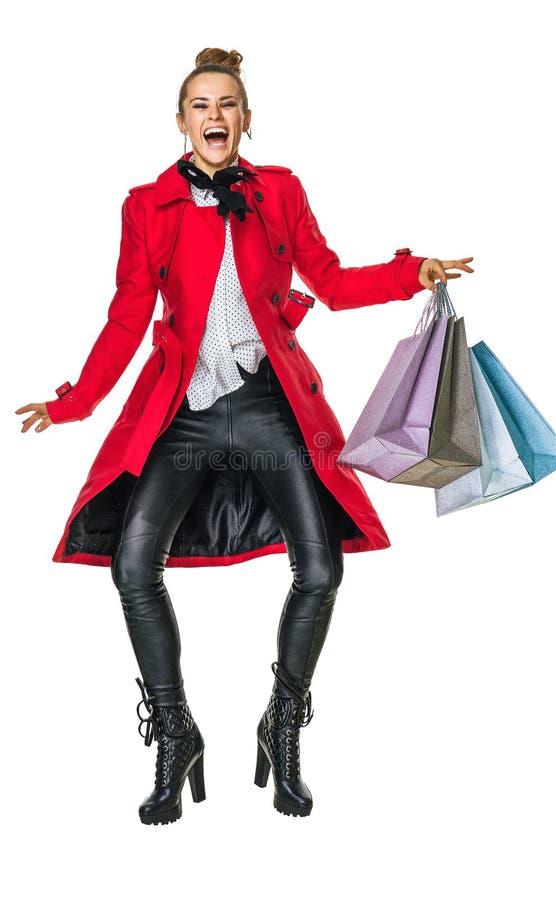 Счастливый современный покупатель женщины в красном пальто на белый скакать стоковые фото
