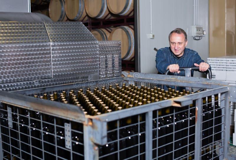 Счастливый создатель вина разгржает контейнеры с бутылками стоковое изображение