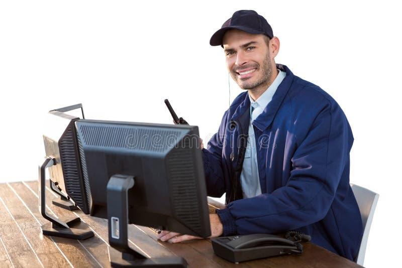 Счастливый сотрудник охраны говоря на рации пока использующ компьютер стоковые изображения