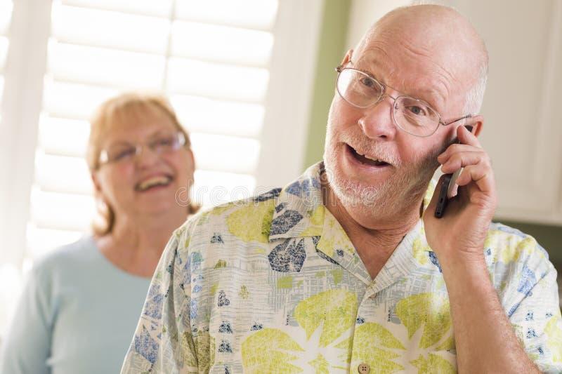 Старший взрослый супруг на сотовом телефоне с супругой позади стоковые изображения rf
