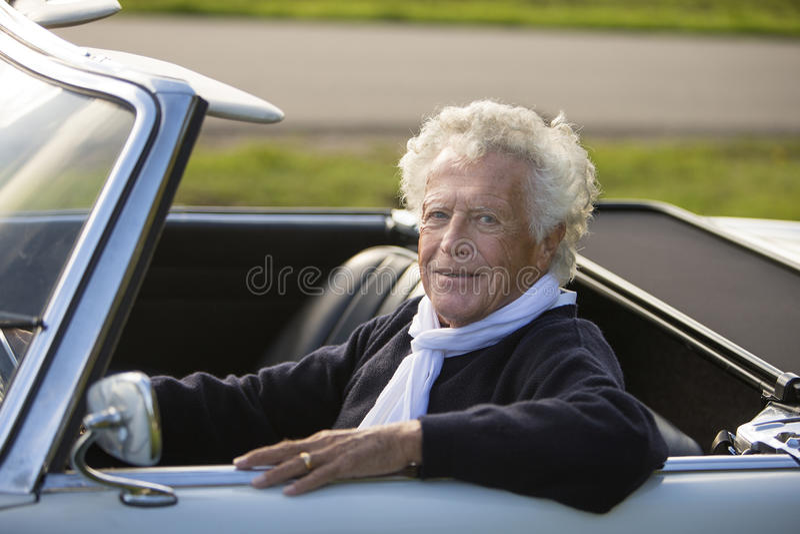 Счастливый старший человек в винтажном автомобиле спорт стоковая фотография rf