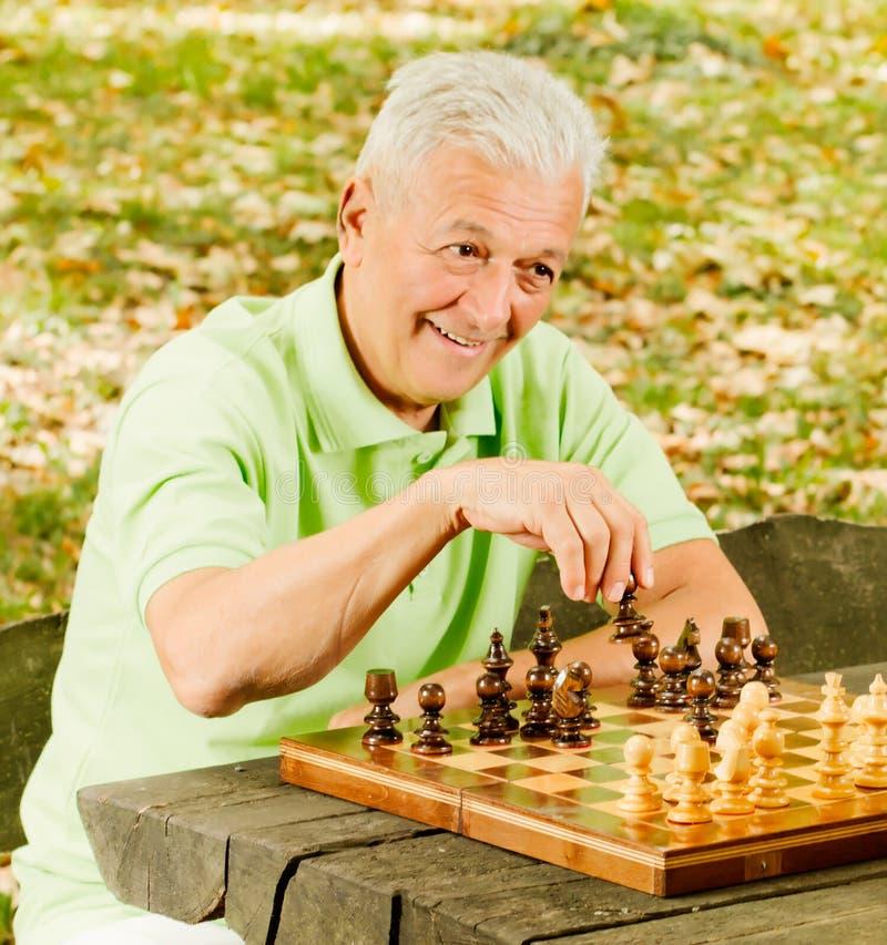 Счастливый старший человек играя шахмат стоковые изображения