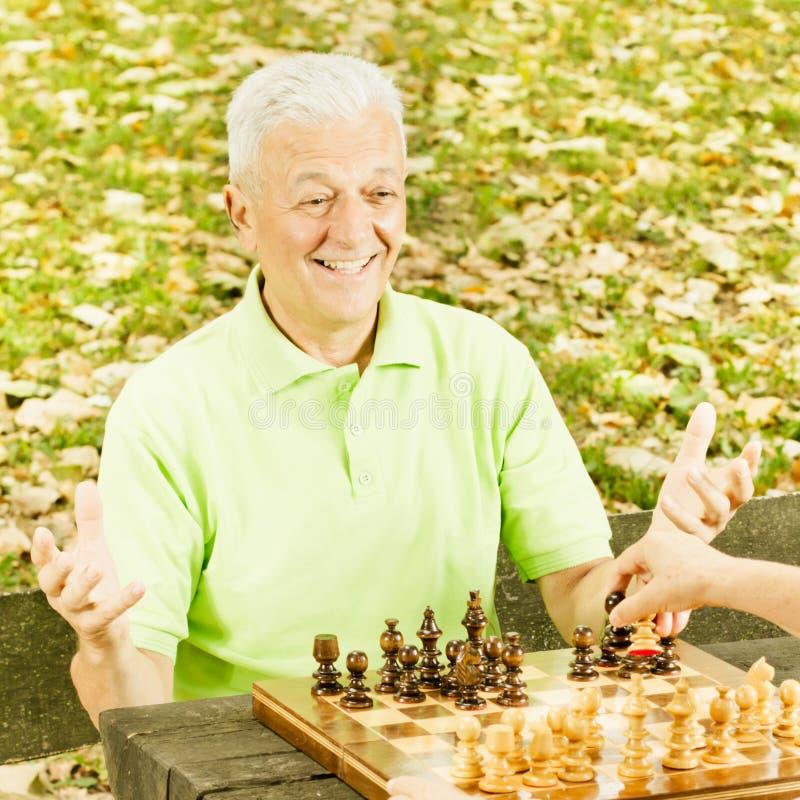 Счастливый старший человек играя шахмат стоковая фотография rf