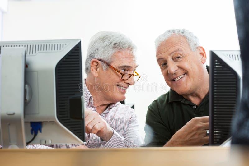 Счастливый старший человек при одноклассник сидя на столе компьютера стоковое фото