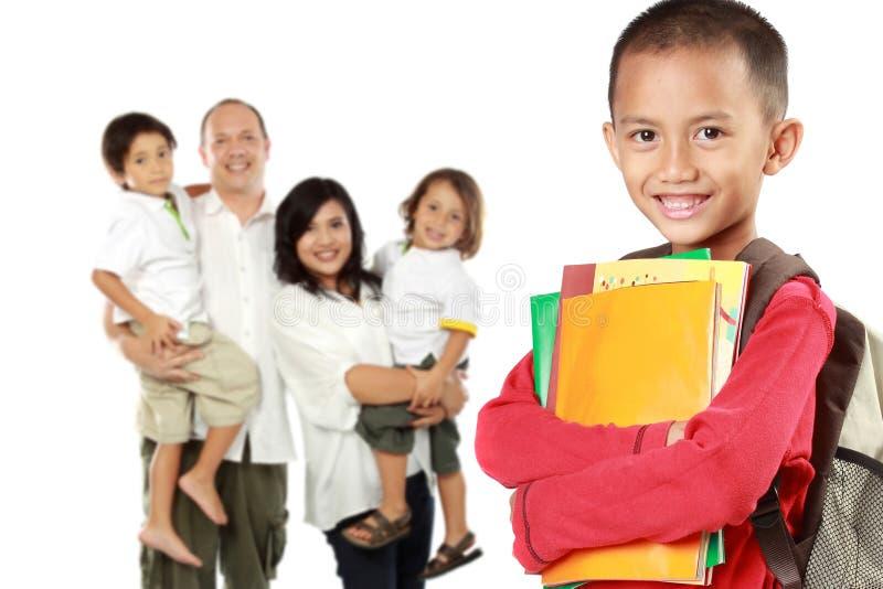 Счастливый студент с книгами и его семьей на suppor предпосылки стоковая фотография
