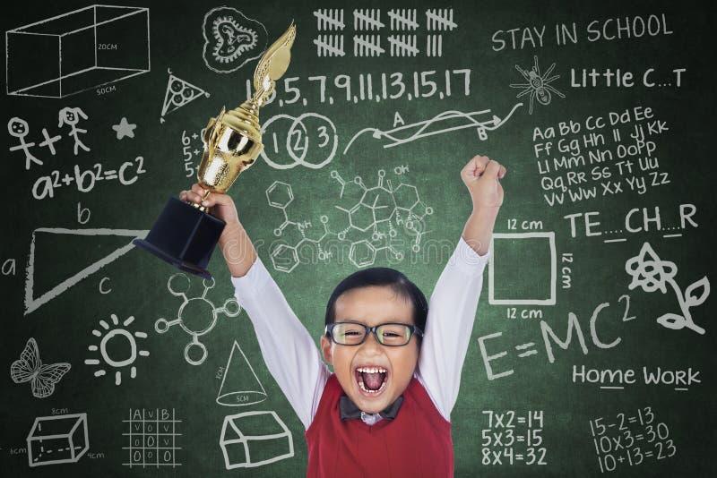Счастливый трофей владением мальчика студента в классе иллюстрация штока