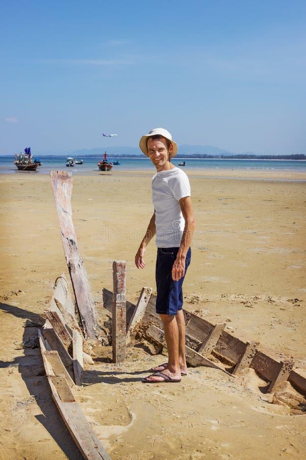 Счастливый турист стоя на разрушенной шлюпке стоковые фото