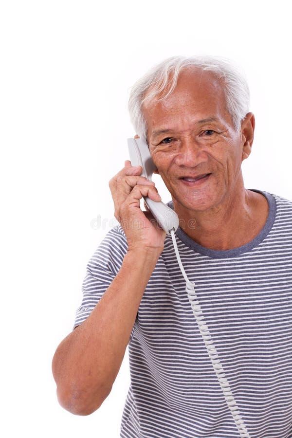 Счастливый, усмехающся, ослабленный старый старший человек используя телефон стоковое фото