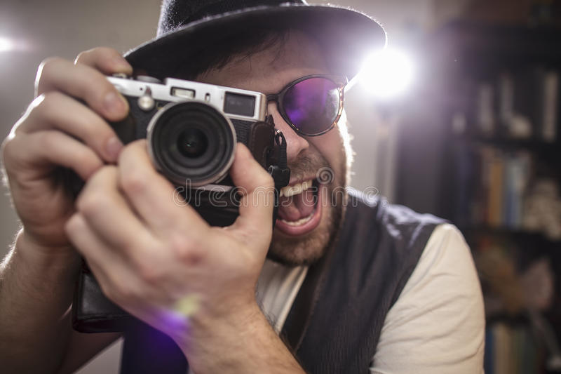Счастливый усмехаясь битник фотографа фотографируя используя старый хлев стоковое фото