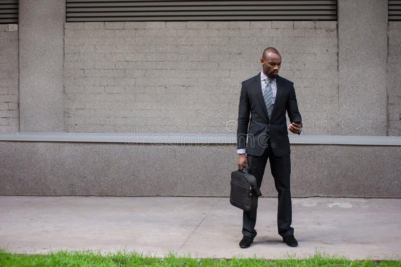 Счастливый усмехаясь городской профессиональный человек используя умный телефон в городском стоковая фотография