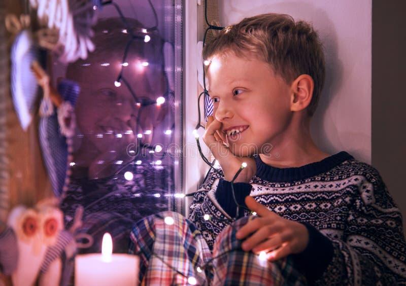 Счастливый усмехаясь мальчик на окне с оформлением рождества освещает стоковые фотографии rf