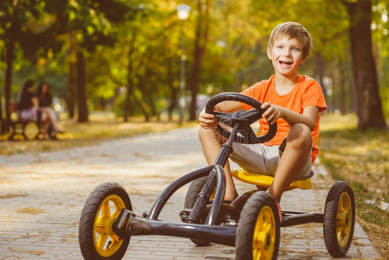 Счастливый усмехаясь мальчик управляя автомобилем игрушки внешним в стоковые изображения rf