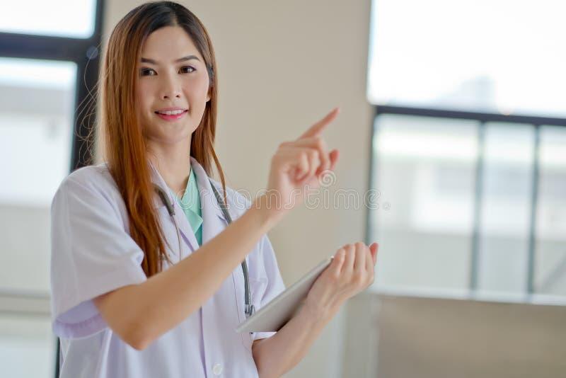 Счастливый усмехаясь молодой красивый женский доктор показывая пустую область f стоковое изображение