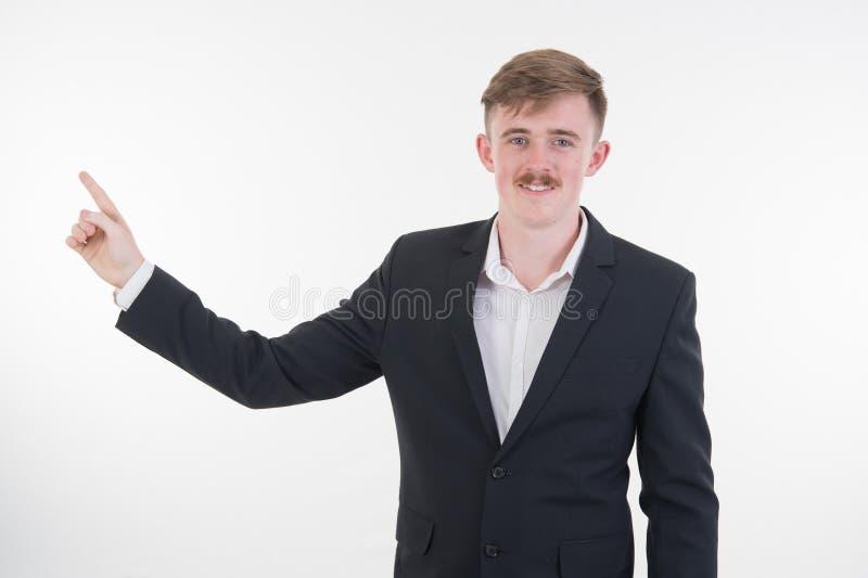 Счастливый усмехаясь молодой человек представляя и показывая ваш текст или побуждает стоковая фотография