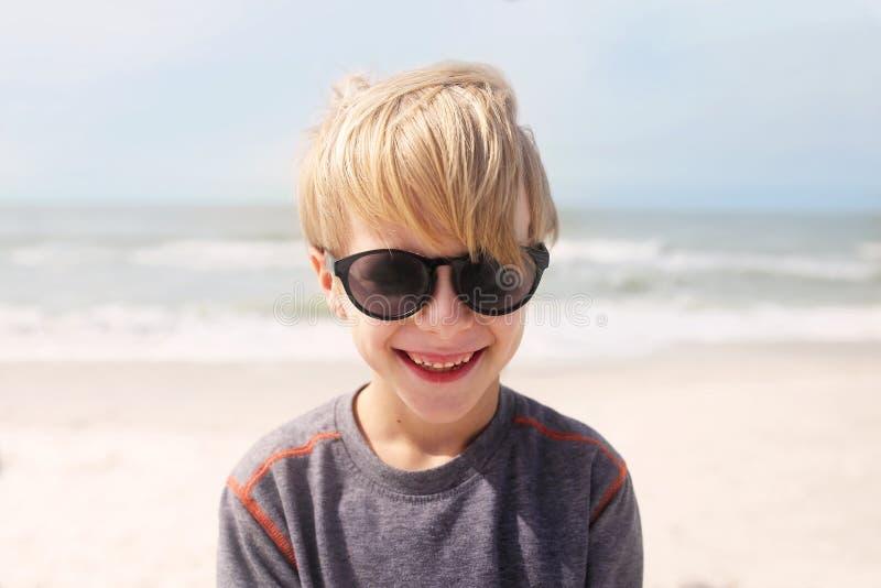 Счастливый усмехаясь ребенок на пляже океаном стоковое фото rf