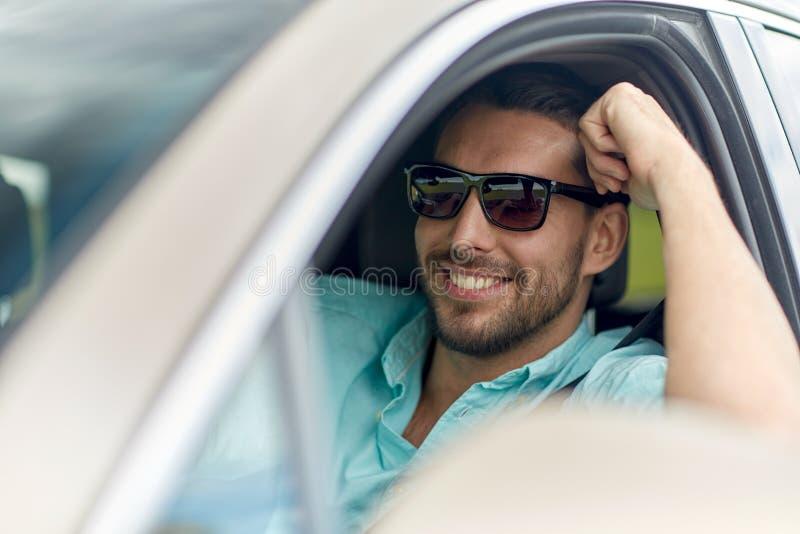 Счастливый усмехаясь человек в солнечных очках управляя автомобилем стоковая фотография rf
