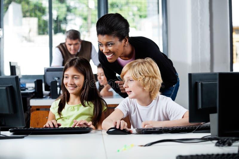 Счастливый учитель помогая школьникам в использовании стоковые изображения rf