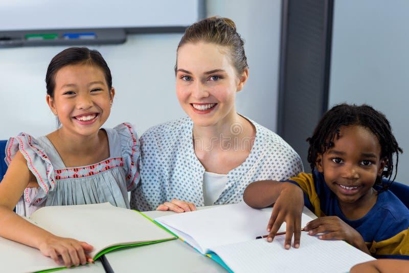 Счастливый учитель с школьниками стоковая фотография rf