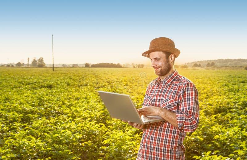 Счастливый фермер с портативным компьютером перед полем стоковое фото rf