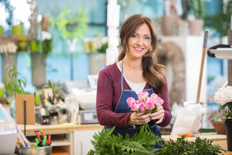 Счастливый флорист делая букет розовых роз в магазине стоковые фотографии rf
