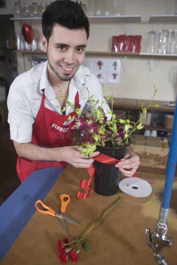 Счастливый флорист украшая вазу цветка стоковая фотография