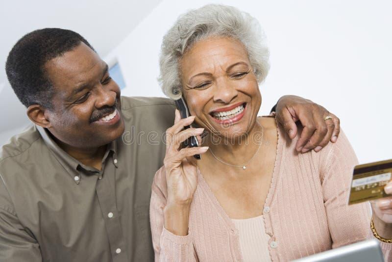 Счастливый ходить по магазинам пар онлайн используя кредитную карточку стоковое фото