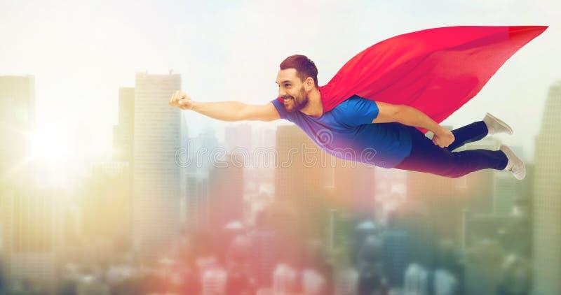 Счастливый человек в красном летании накидки супергероя на воздухе стоковое фото