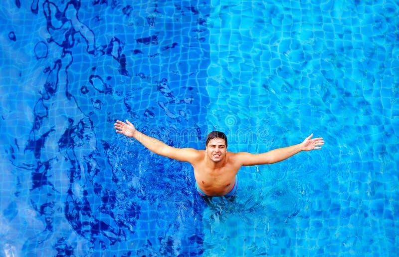 Счастливый человек наслаждаясь каникулами, пока стоящ в воде бассейна, взгляд сверху стоковые изображения rf