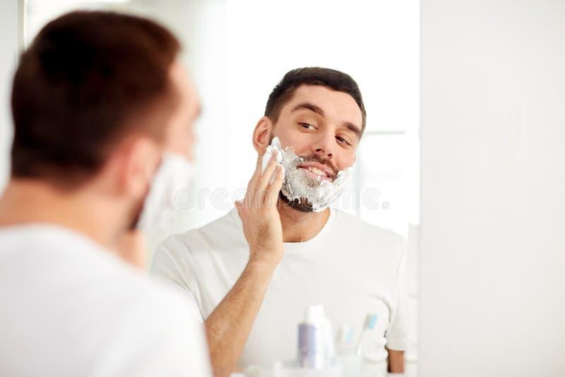 Счастливый человек применяясь бреющ пену на зеркале ванной комнаты стоковое изображение rf