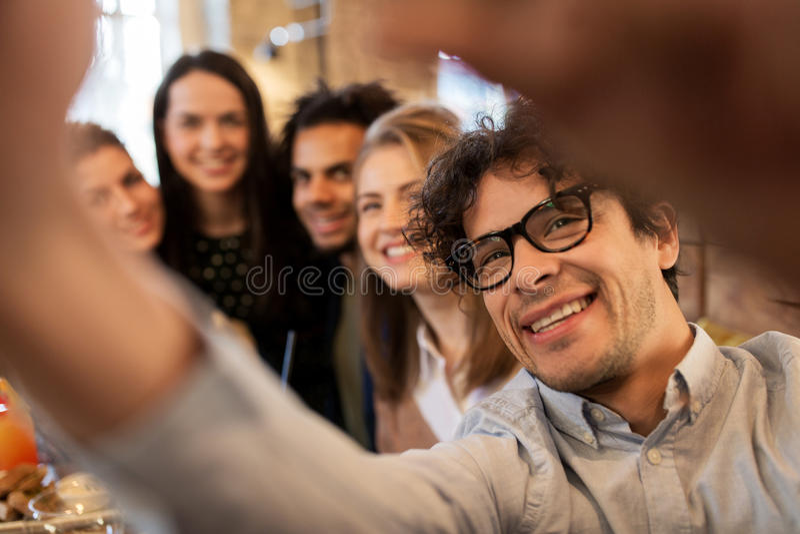 Счастливый человек принимая selfie с друзьями на ресторан стоковая фотография rf