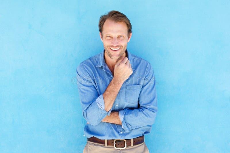 Счастливый человек смеясь над против голубой предпосылки стоковое изображение