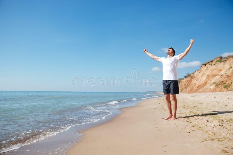 Счастливый человек стоя barefoot на пляже при протягиванные руки стоковые изображения rf
