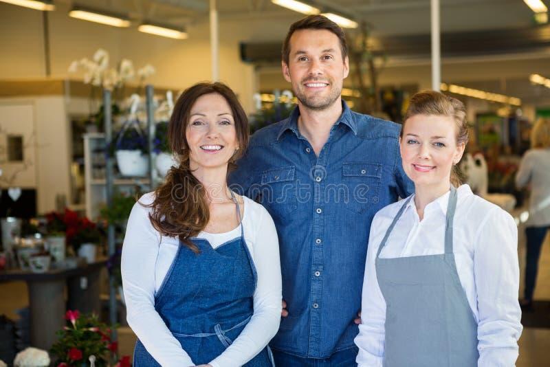 Счастливый человек с Salesgirls в цветочном магазине стоковые изображения