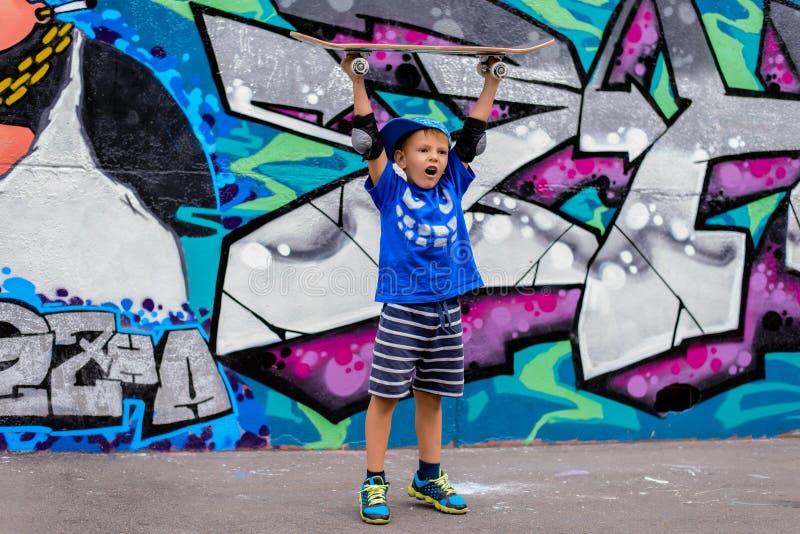 Счастливый шаловливый мальчик держа его скейтборд стоковые изображения