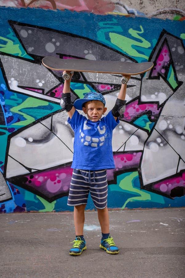 Счастливый шаловливый мальчик держа его скейтборд стоковое изображение rf