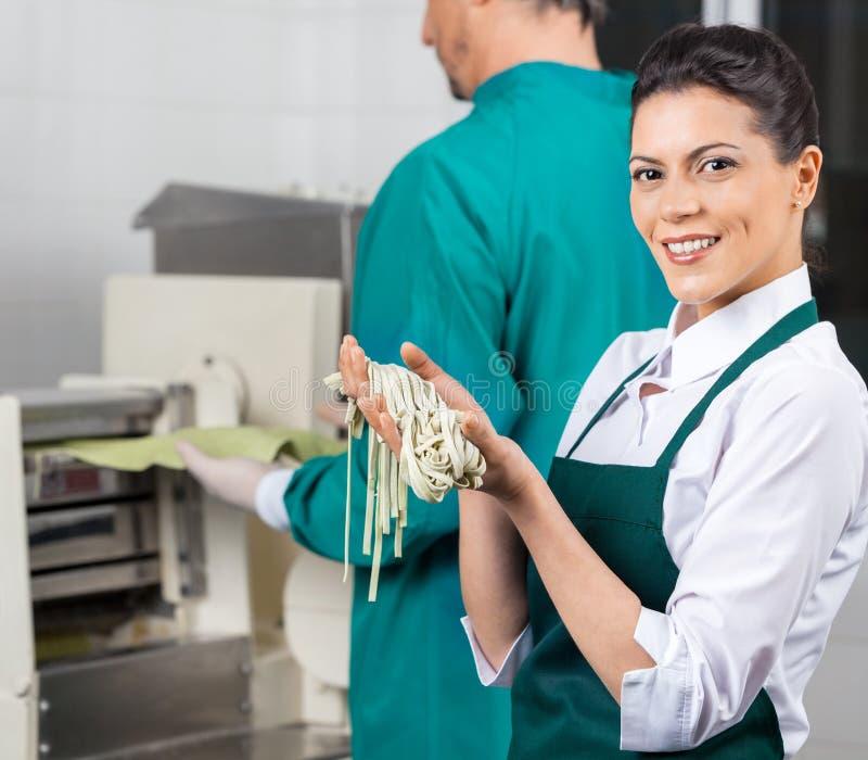 Счастливый шеф-повар держа свежие макаронные изделия спагетти внутри стоковое фото rf