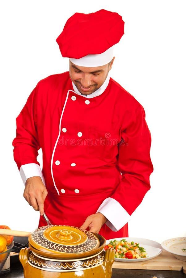 Счастливый шеф-повар подготавливая еду стоковая фотография