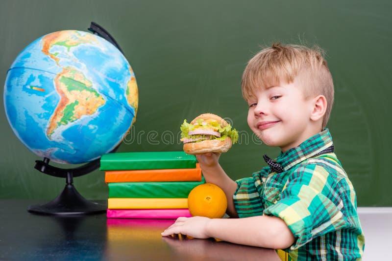 Счастливый школьник пока имеющ обед во время стоковые изображения rf