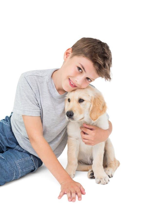 Счастливый щенок обнимать мальчика стоковые изображения rf