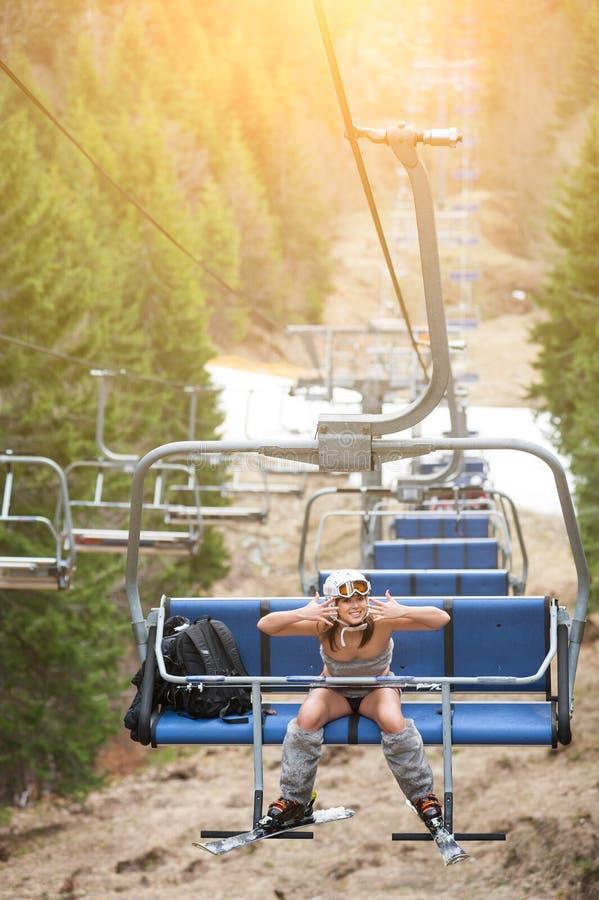 Счастливый лыжник девушки сидит на подъеме лыжи и едет до верхней части горы стоковые изображения rf