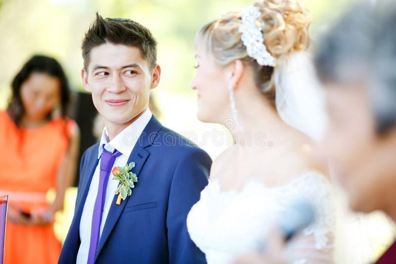 Счастливый groom смотрит невесту во время свадебной церемонии стоковое изображение